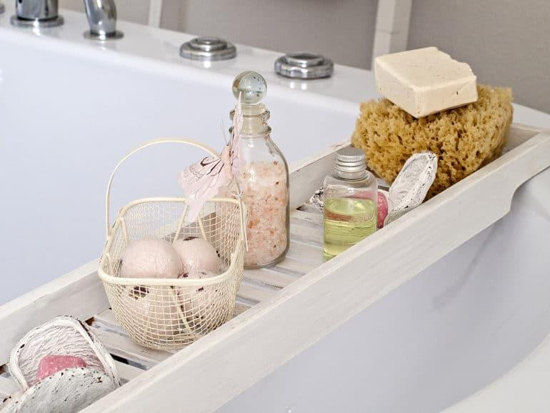 verschiedene Badesalzprodukte auf einer Badewannenablage aus Holz