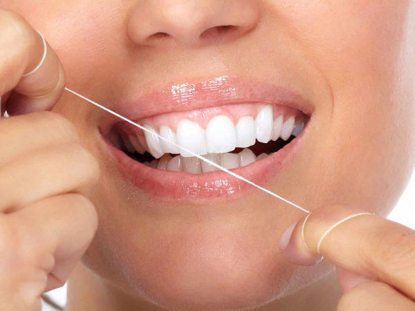 Frau hält Stück Zahnseide vor dem Mund