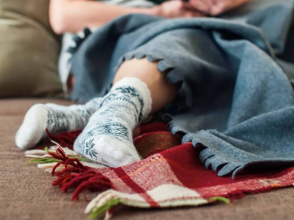 Frau sitzt mit warmen Füßenn auf Sofa