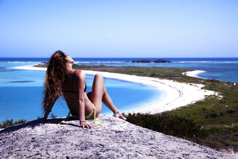 Frau sonnt sich mit Blick auf Strand