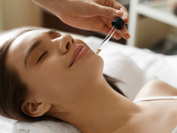 Face Skin Care. Closeup Of Beautiful Smiling Woman Receiving Serum Oil Treatment In Beauty Salon. Cosmetologist Applying Cosmetic Serum On Girl's Face At Cosmetology Center. High Resolution Image